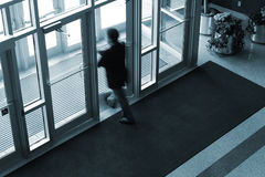 Into the Light. Motion blur of businessman exiting an office building Stock Photography