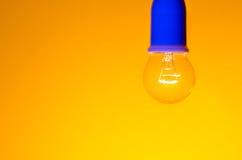 Light. Close up of light bulb against orange background - shallow depth of field Stock Image