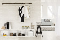 Light and air filling contemporary hallway space. Young woman's hallway arranged in black and white, with recyclable furniture and clothing items, bordering a Royalty Free Stock Images