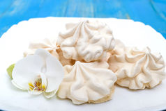 Light air vanilla meringue on a white plate with orchid flower on a blue background. Stock Photo
