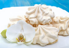 Light air vanilla meringue on a white plate with orchid flower on a blue background. Stock Photos