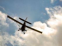 Light aircraft flying away to the sky. Dark, light aircraft flying away to the clouds and sky. Photo of piston oldtimer airplane on the cloudy sky. From behind Royalty Free Stock Photos