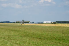 Light aircraft. Light silver airplane lands in airport. Sunny summer day and blue sky Royalty Free Stock Image