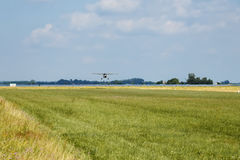 Light aircraft. Light silver airplane lands on airport. Sunny summer day and blue sky Stock Photography