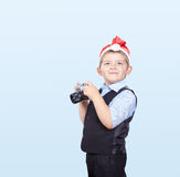 On a light background Boy in Santa Claus cap is keeping a camera in the hand Royalty Free Stock Photography