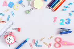 On a light background in the center is an empty place for an inscription, mock up. Colorful clerical and school supplies. Are scattered around. Layout for the stock image