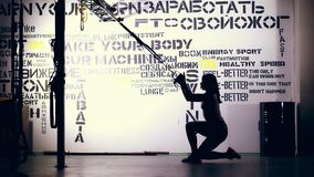 On a light background, a dark figure, the outline of a woman in leggings and top performs exercising on TRX loops stock video footage