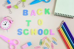 On a light background the inscription Back to school. Around it are various colored pencils, scissors, paperclips stock photos
