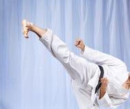 On a light background a man beats a high kick. Leg Royalty Free Stock Photos