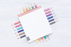 Light background with space for writing, with a set of colored pencils and a sheet of paper on them Royalty Free Stock Photo
