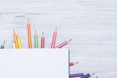 On a light background of the table, there is a checkered paper on colored pencils. stock image