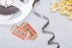On a light background, unwound film with two tickets to the cinema and fresh popcorn royalty free stock image