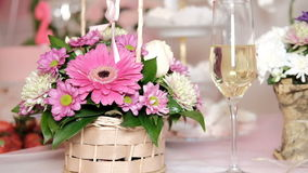 Light banquet with drinks, sweet things on sea shore Served table. On fresh air outdoors. Vases with fruits, strawberries. On foreground colorful bouquets stock video footage