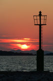 Light beacon. With sea and red sunset in background Royalty Free Stock Images