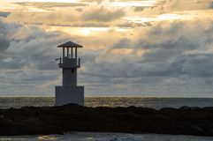 Light beacon at sunset. With dramatic clouds in the background Stock Photos