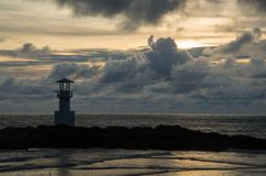 Light beacon at sunset. With golden sky in the background Royalty Free Stock Photos
