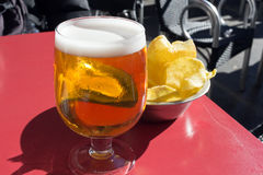 Light beer and chips on outdoors table cafe - Taken in Madrid. Potato chips and cerveza, in the spanish bar royalty free stock photos