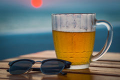Light beer in a circle. Sea. Cold Draught Beer with bokeh of the sunset in the sea background Royalty Free Stock Photography