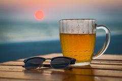 Light beer in a circle. Sea. Cold Draught Beer with bokeh of the sunset in the sea background Stock Photo