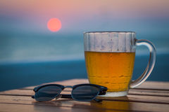 Light beer in a circle. Sea. Cold Draught Beer with bokeh of the sunset in the sea background Stock Image