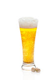 Light beer with the foam in a glass and pistachios Stock Images