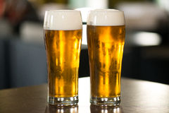 Light beer. Glass of light beer on a dark pub stock photography