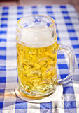 Light Beer in a glass pint mug served on a wooden. Fresh cold golden light beer with froth served in a glass pint mug on a traditional German blue and white Royalty Free Stock Photo