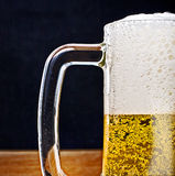Light Beer in a glass pint mug served on a wooden Royalty Free Stock Photography
