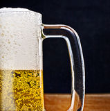 Light Beer in a glass pint mug served on a wooden royalty free stock photos