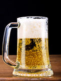 Light Beer in a glass pint mug served on a wooden stock photo