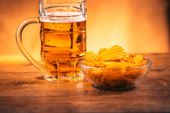 Light beer mug with a bowl of potato chips on a wooden table Royalty Free Stock Photo