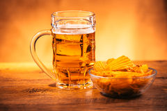 Light beer mug with a bowl of potato chips on a wooden table Royalty Free Stock Image