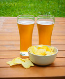 Light  beer with potato chips on  table Royalty Free Stock Image