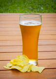 Light  beer with potato chips on wooden table Stock Photos
