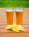 Light  beer with potato chips on a wooden table Royalty Free Stock Images