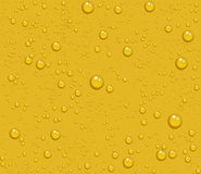 Light beer transparent drops of dew on yellow background Royalty Free Stock Image