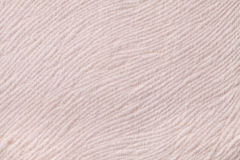 Light beige background from soft textile material. Fabric with natural texture. Light beige background from a soft wool textile material closeup. Fabric with Royalty Free Stock Photography