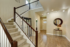 Light beige hallway interior. Carpeted staircase, hardwood floor, console table with mirror and entrance door on the background. Northwest, USA Stock Images