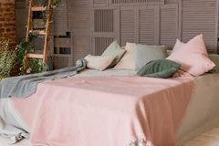 Light beige pink blanket on bed with green mint pillows. Stylish cozy scandinavian bedroom interior: bed, wooden ladder stock image