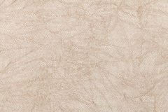 Light beige wavy background from a textile material. Fabric with natural texture closeup. Upholstery fabric pleated royalty free stock image