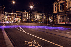 Light from bicycle wheel on street in night Amsterdam. Stock Photos