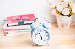 Light blue alarm clock on wooden table with books and glasses Stock Photos
