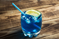 Light blue alcoholic drink curacao liqueur. On wooden background royalty free stock image