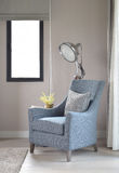 Light blue armchair with gray pillow and retro lamp in the living room Stock Photos