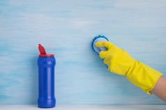 On a light blue background, a hand in a yellow rubber glove, brushes the surface, next to it is an open blue bottle with cleaning royalty free stock photography