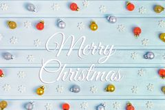 On a light blue background the inscription Merry Christmas. Lots of small golden, silver and red balls. Decorative. Snowflakes. Christmas composition, frame stock images
