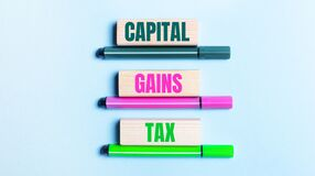 On a light blue background, there are three multi-colored felt-tip pens and wooden blocks with the CAPITAL GAINS TAX