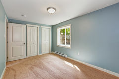 Light blue bedroom with closets. Empty small room with light blue walls and brown carpet floor. Room has closets stock photos