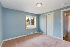 Light blue bedroom with closets. Empty small room with light blue walls and brown carpet floor. Room has closets stock photo