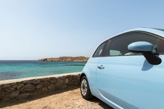 Light blue rental car parked next to the sea in Mykonos island, Greece. Light blue car parked next to the sea in Mykonos island, greece. Wide angle lens shot Royalty Free Stock Image